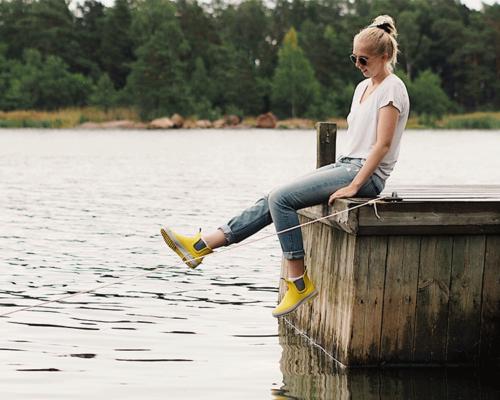 tyttö istuu laiturin reunalla keltaiset Hai Lowt jalassa